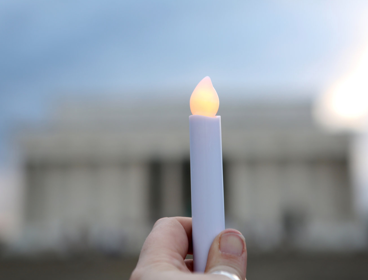 A candle is held in focus with the out of focus Lincoln Memorial in the background.