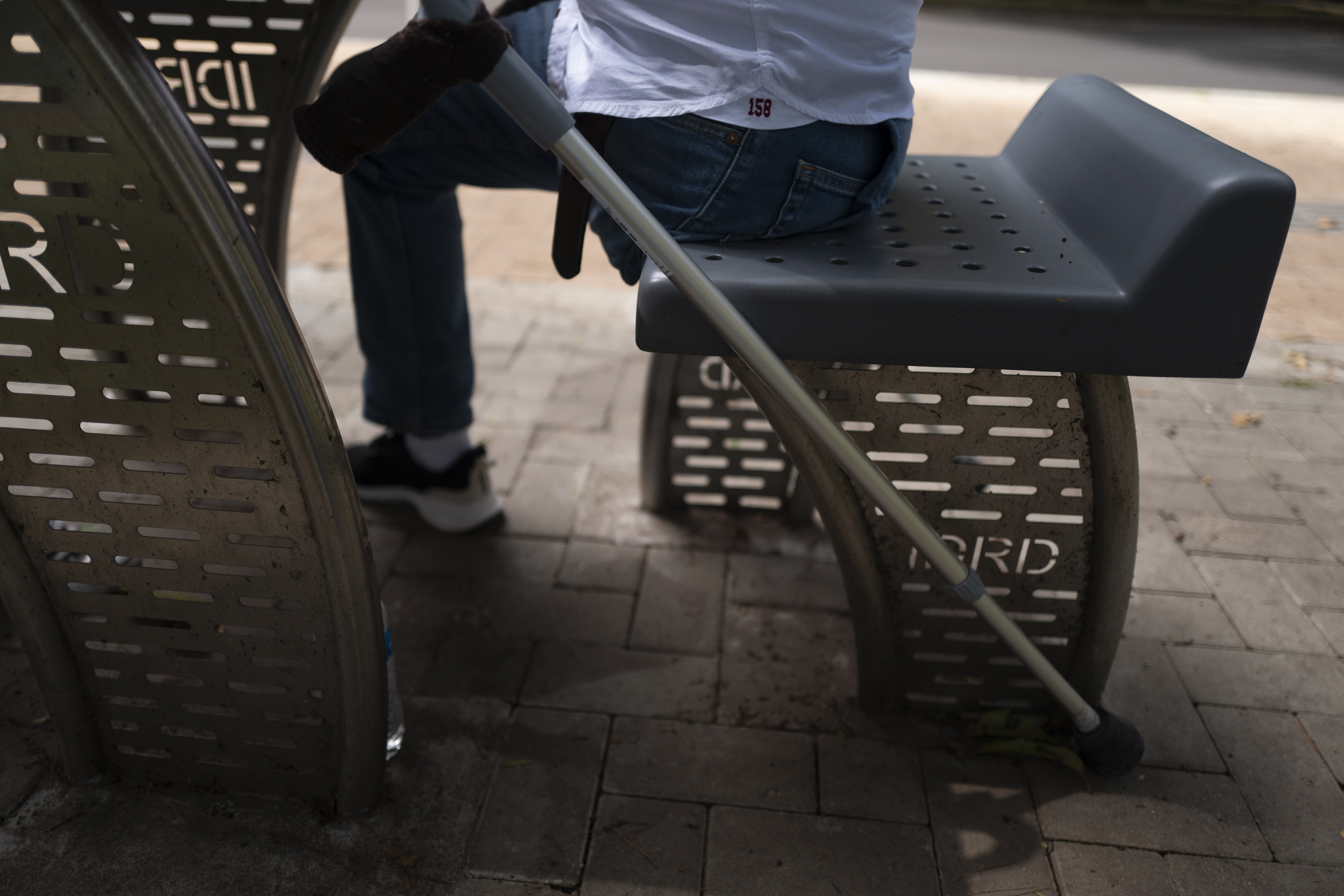 man seated at a park bench showing torso down view of amputated leg
